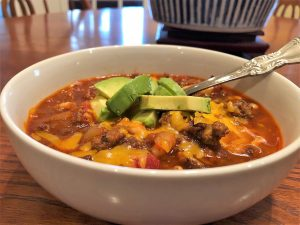 Bowl of chili with cheese and avocado toppings